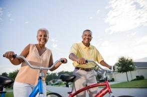 Senior African American couple with bicycles on residential street